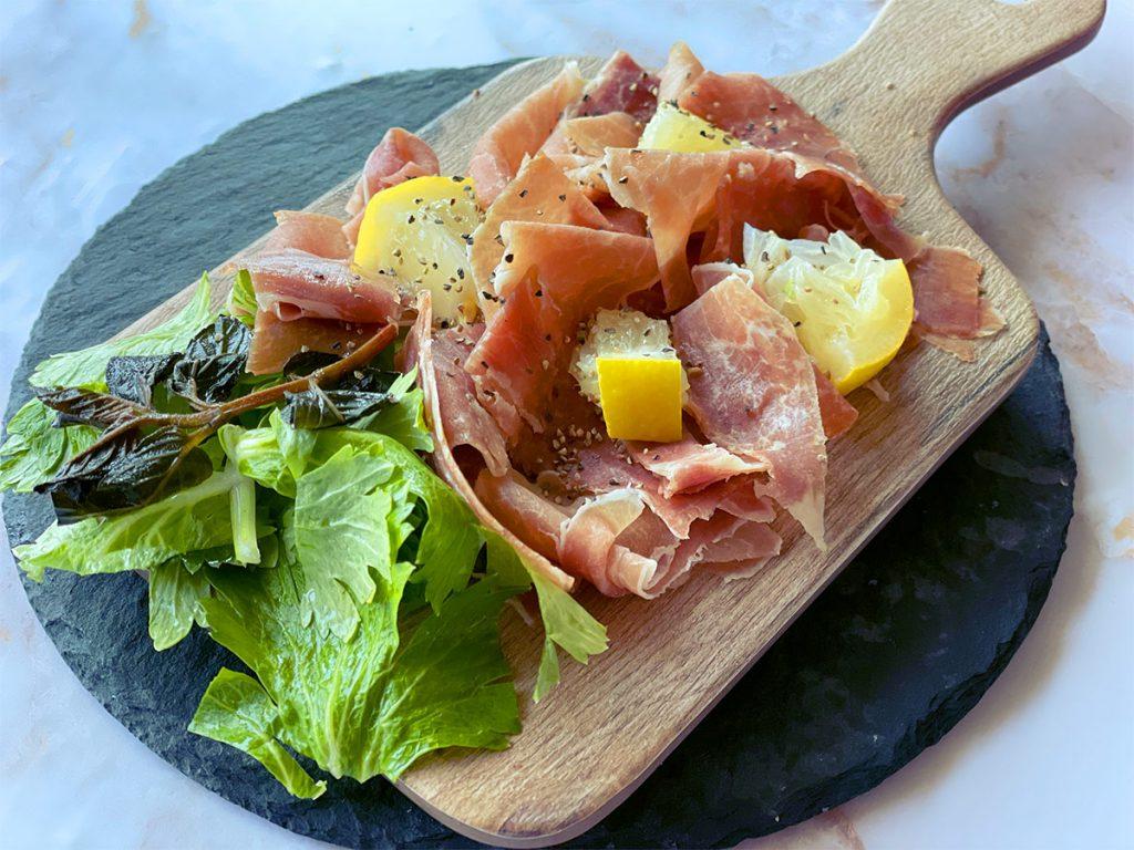 佐助豚の生ハムをウッドプレートにレモンと盛り付けた様子